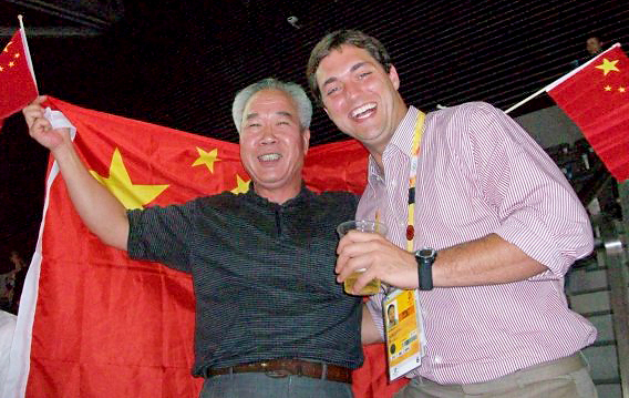 "Beijing Olympics (2008): Sam is inside the ""Bird's Nest"" stadium with a friendly Chinese man after watching Usain Bolt break the world record in the 100m."